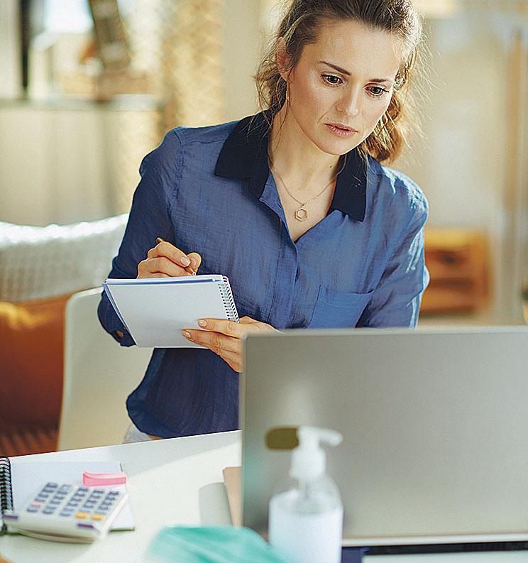 Frau, die vor einem Laptop sitzt und sich Notizen macht.
