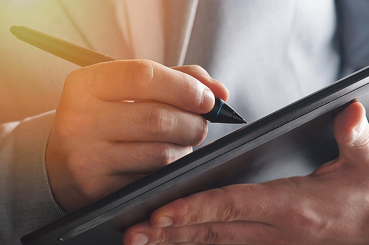 Bildausschnitt einer Hand, die mit einem Stift auf einem Tablet unterschreibt.