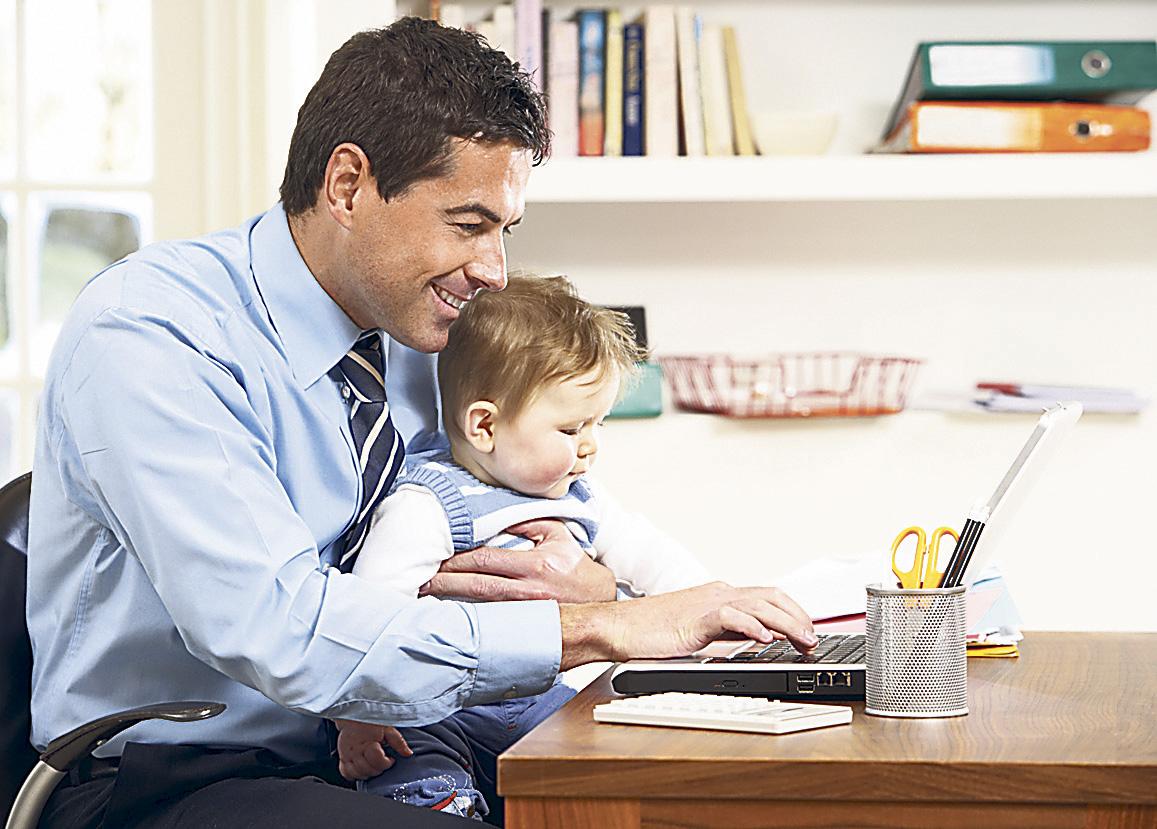 Mann im Home Office sitzt mit seinem Kind vor einem Laptop. Thema: Future Work