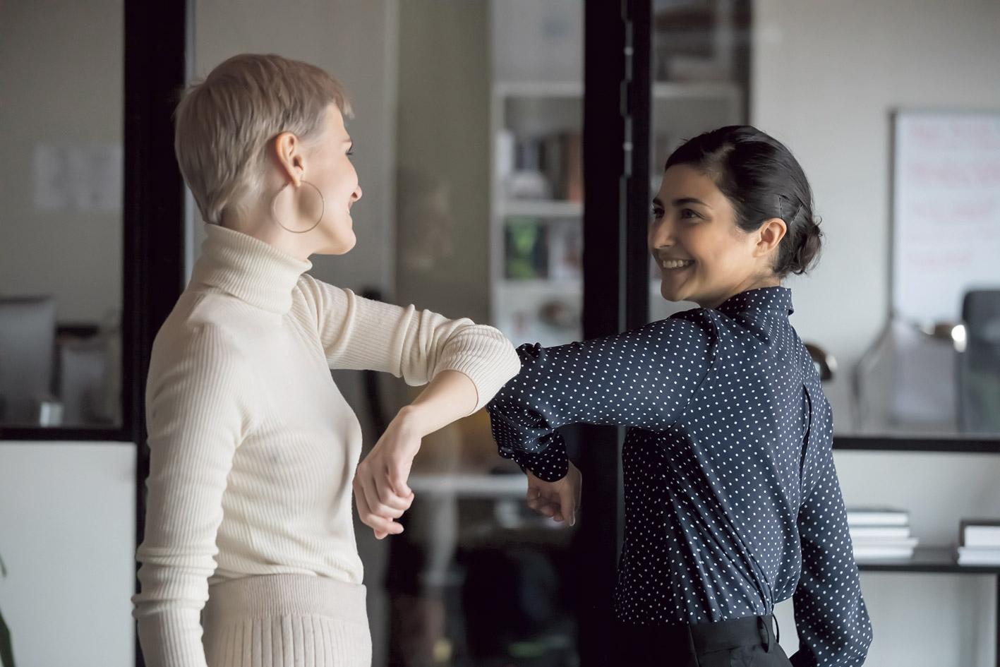 Zwei Kolleginnen begrüßen sich corona-konform mit den Ellenbogen