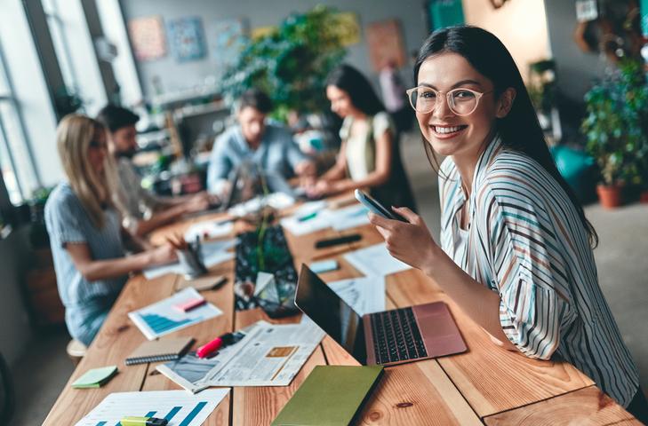Junge Mitarbeiter arbeiten gemeinsam an einem großen Tisch