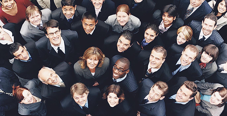 Viele Mitarbeiterinnen und Mitarbeiter mit verschiedenen ethnischen Hintergründen schauen nach oben in die Kamera. Thema: Diversity-Management