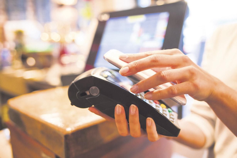 Mobile Payment: Das Smartphone wird an ein lesefähiges Gerät gehalten.