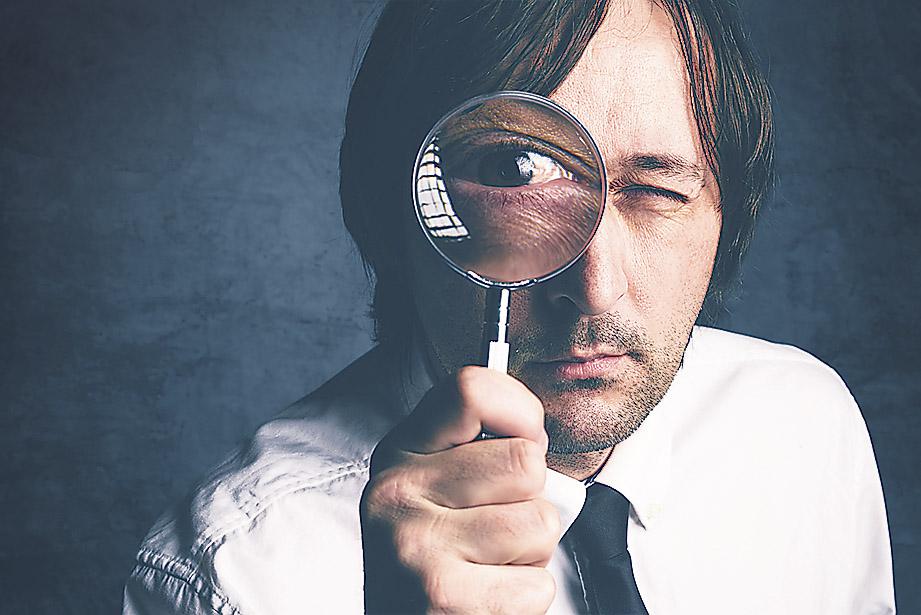 Mann schaut durch eine Lupe in die Kamera. Thema: Standortanalyse