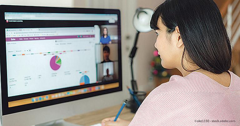 Frau, die am Computer sitzt und arbeitet.