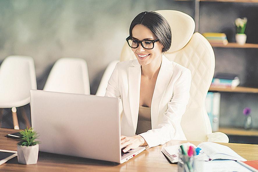 Frau, die am Schreibtisch sitzt und am Laptop arbeitet.