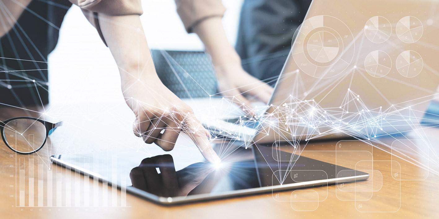 Nahaufnahme: Laptop und Tablet, welche beide gleichzeitig von einer Sekretärin bedient werden. Thema: Bürosoftware