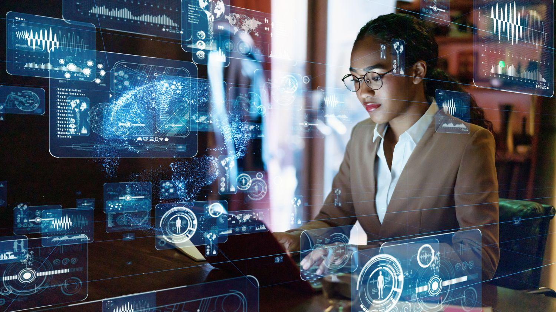 Frau, die am Laptop sitzt, von abstrakten Darstellungen umgeben