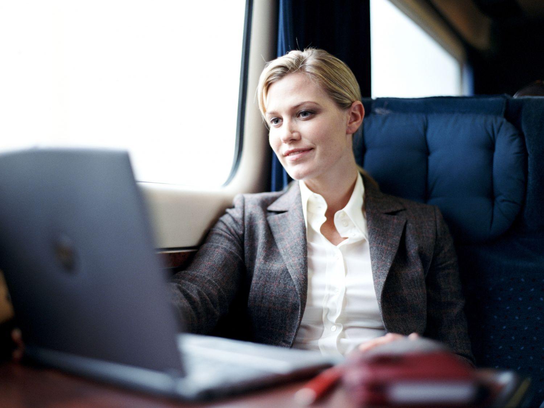 Geschäftsreisende sitzt im Zug und arbeitet am Laptop. Thema: Geschäftsreise planen