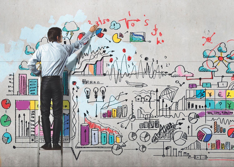 Ein Mann malt und schreibt Tabellen und Diagramme auf eine Wand.