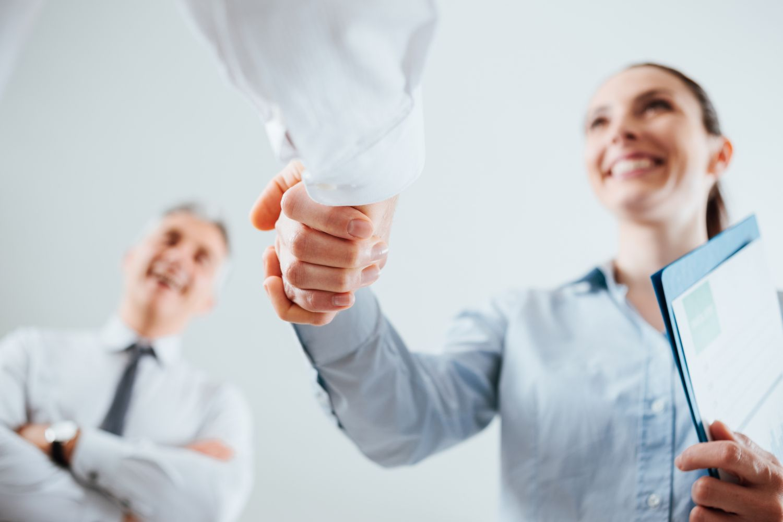 Einer Mitarbeiterin wird die Hand geschüttelt. Thema: Employer-Branding