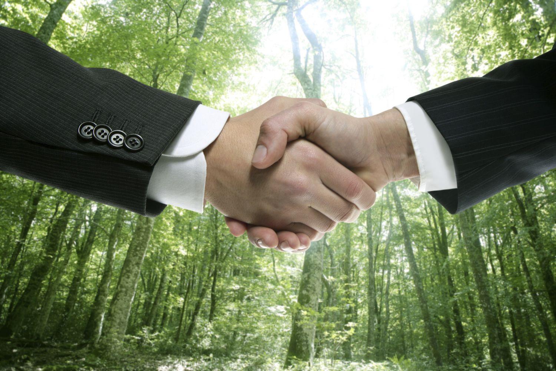 Detailaufnahme: Hände zweier Geschätsleute halten sich fest wie zum Handschlag. Thema: Corporate Social Responsibility