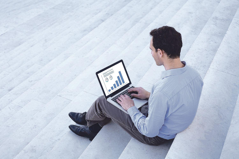 Ein Mann sitzt mit seinem Laptop auf den Stufen einer Treppe.