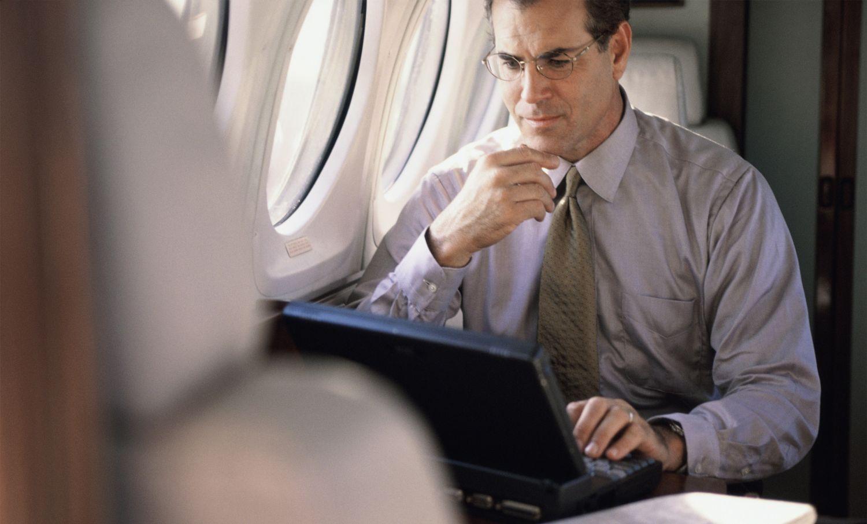 Geschäftsmann im Flugzeug arbeitet am Laptop. Thema: Nach der Reise