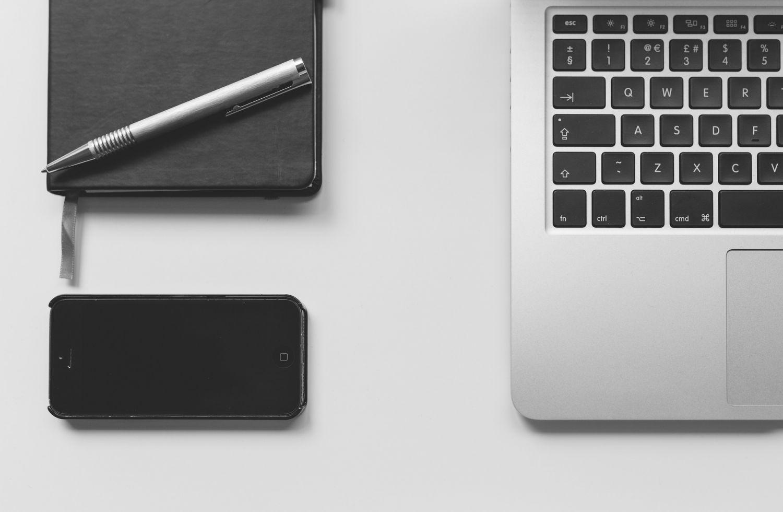 Detailaufnahme: Smartphone, Macbook und Terminplaner