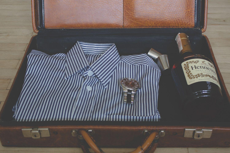Vor der Reise muss der Koffer gepackt werden. Business-Hemd, Uhr und ein Wein als Gastgeschenk.