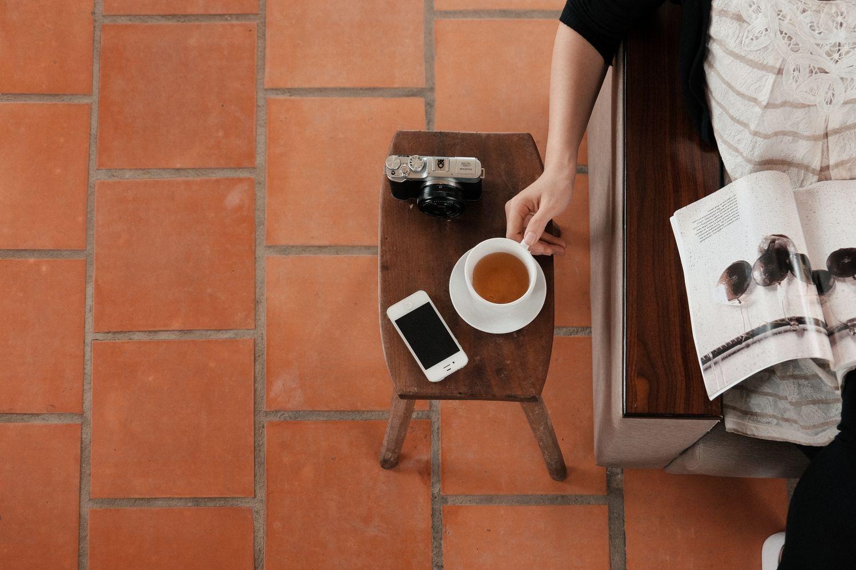 Zeitungsleserin; Teetasse und Smartphone befinden sich neben ihr auf einem Beistelltisch. Thema: Finanztechnologien