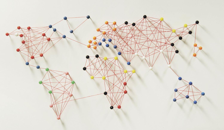 Stecknadeln und Fäden sind zu einer Weltkarte angeordnet. Thema: Smart leben