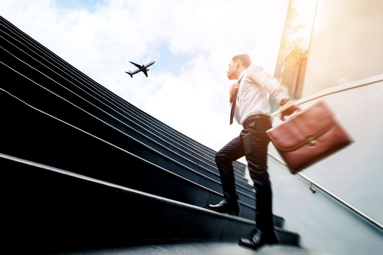 Geschäftsmann mit Aktentasche steigt eine Treppe hinauf. Im Himmel über ihm ist ein Flugzeug zu sehen.