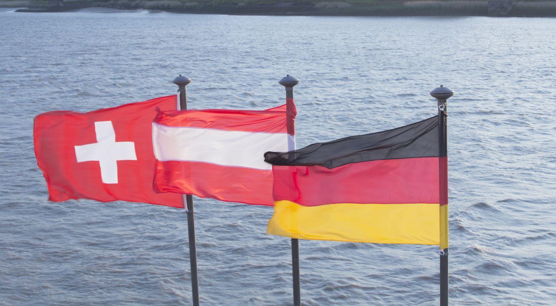 Die Flaggen der Schweiz, Österreich und Deutschland vor einem See. Thema: Standortmarketing