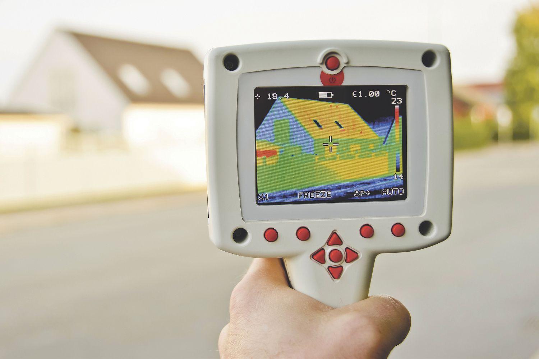 Wärmebildkamera untersucht ein Haus. Thema: Energieeffizienz
