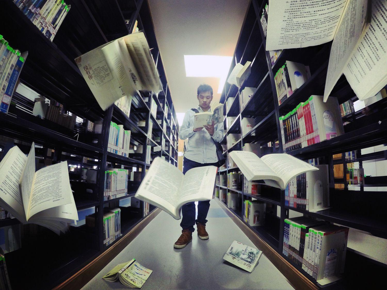 Bücher fliegen aus einem Bücherregal in der Bibliothek