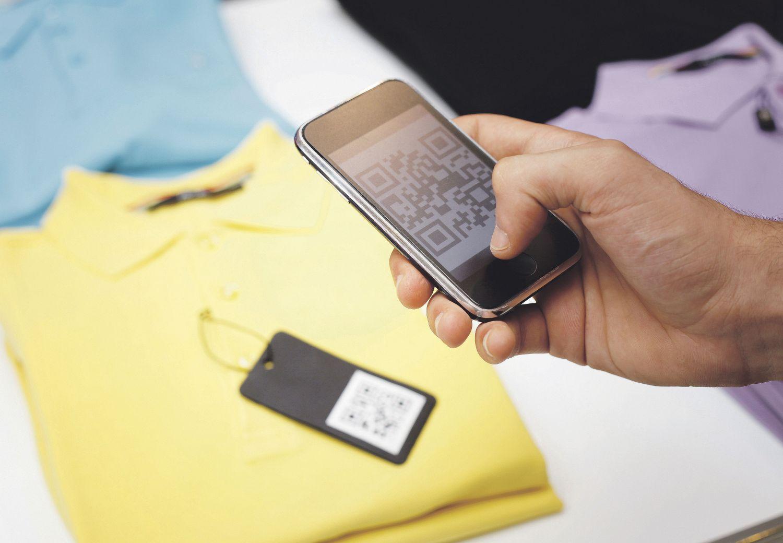 Jemand fotografiert den QR-Code auf dem Preisschild eines Oberteils. Thema: Geschäftsmodellinnovationen