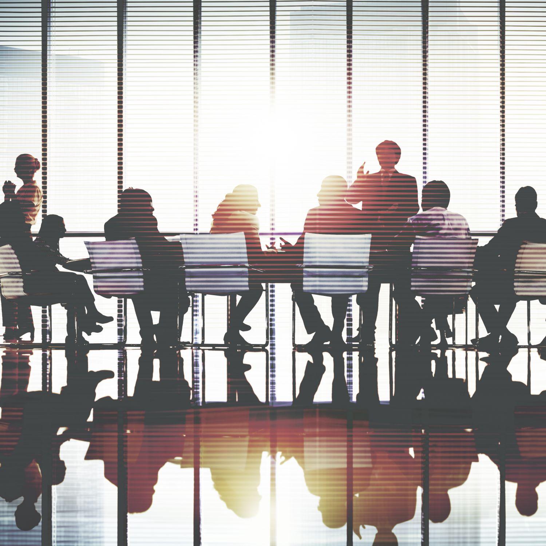Mehrere Personen befinden sich in einem Meetingraum. Thema: Cluster