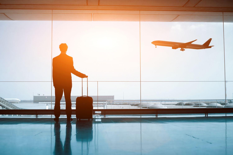 Geschäftsreisender steht am Flughafen und sieht ein Flugzeug abheben. Thema: Travel-Management