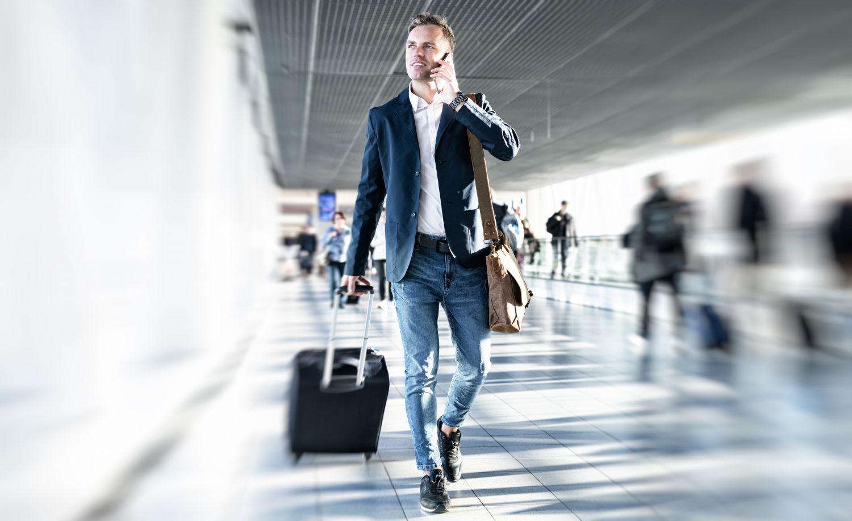 Geschäftsreisender telefoniert und läuft mit seinem Koffer einen Gang entlang. Thema: Reisemittel