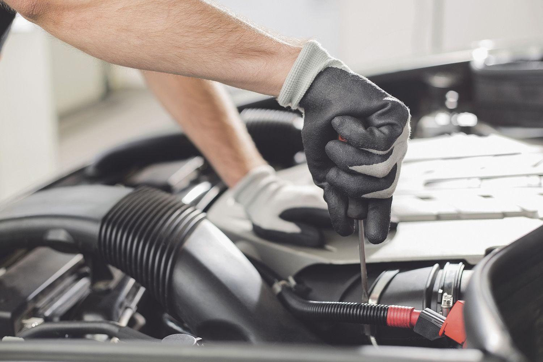 Mechaniker schraubt unter der Motorhaube eines Autos. Thema: Versicherung für den Fuhrpark
