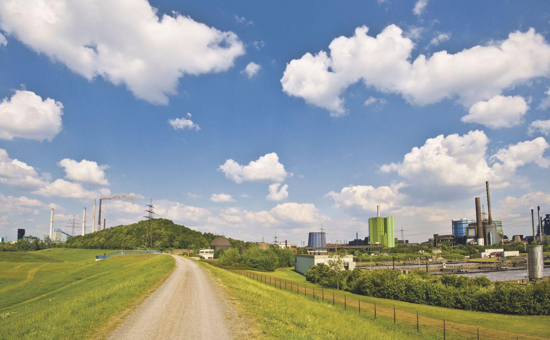 Eine Landstraße, die an einem Industriegelände vorbeiführt, unter blauem Himmel