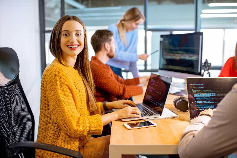 Junge Frau lächelt offen in die Kamera während sie am Schreibtisch sitzt und programmiert. Thema: IT-Fachkraft