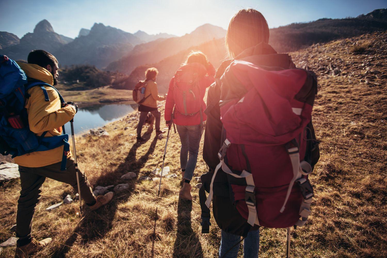 Vier Personen gehen an einem Bergsee wandern. Thema: Incentive-Reisen