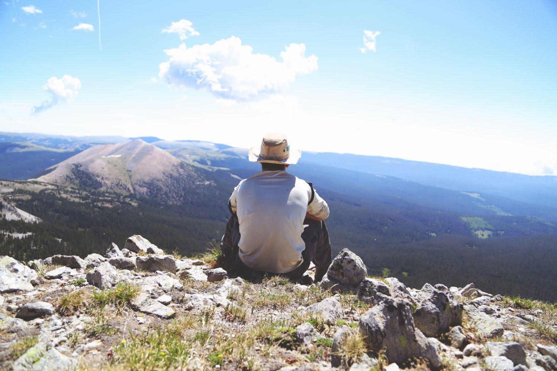 Mann sitzt auf einem Berg und schaut sich die Landschaft an. Thema: Dynamisierung