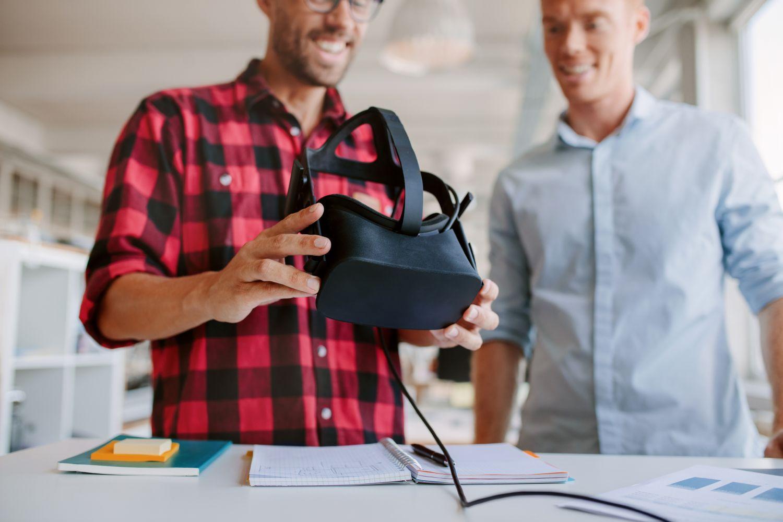 Zwei Männer tauschen sich über eine VR-Brille aus. Thema: Konjunktur in den neuen Bundesländern