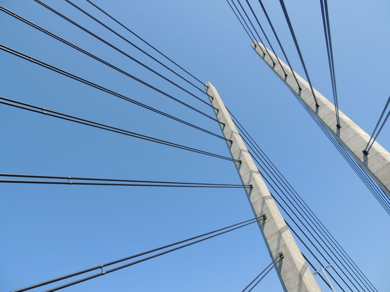 Zwei Brückenpfeiler von unten fotografiert. Thema: Cloud-Technologie