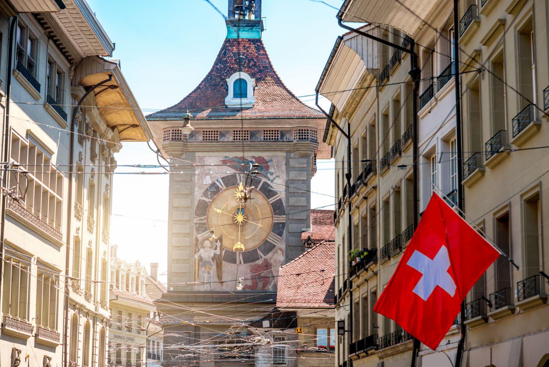 Berner Uhrenturm mit einer Schweizer Flagge im Vordergrund.