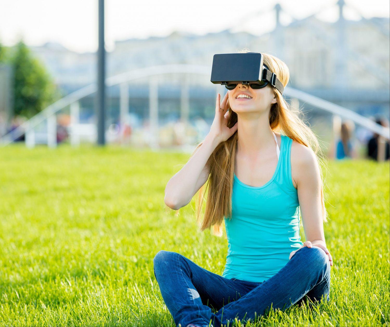 Junge Frau sitzt in einem Stadtpark und schaut sich etwas mit einer VR-Brille an. Thema: Smart City