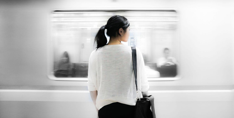 Eine junge Asiatin steht vor einem einfahrenden Zug. Thema: Geschäftsabschluss