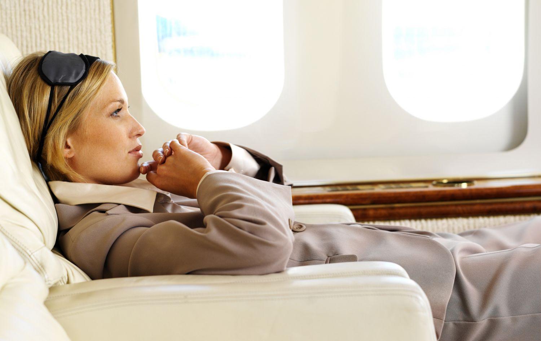 Eine junge Frau mit Schlafmaske in ihrem Sitz im Flugzeug.